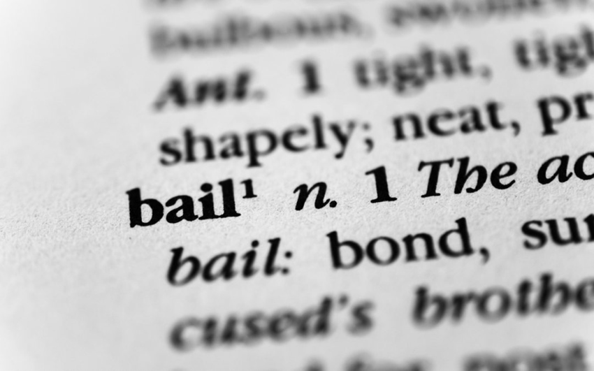 Close-up of the word 'bail' in dictionary with beginning of adjacent definition