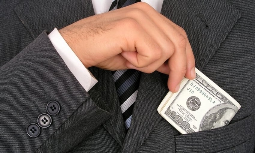 Businessman slipping hundred dollar bills into breastpocket of expensive suit
