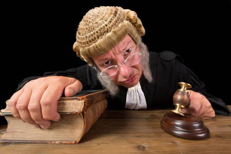 Judge in old-fashioned wig gripping bible and gavel leans forward with menacing expression
